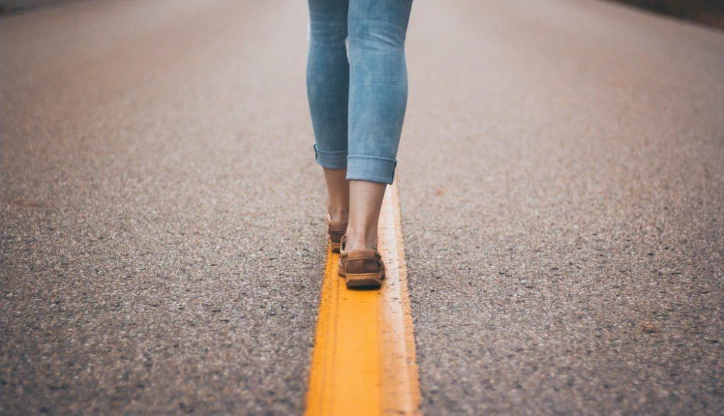 アスファルトに引かれた黄色い線に沿って歩く女性の後ろ姿
