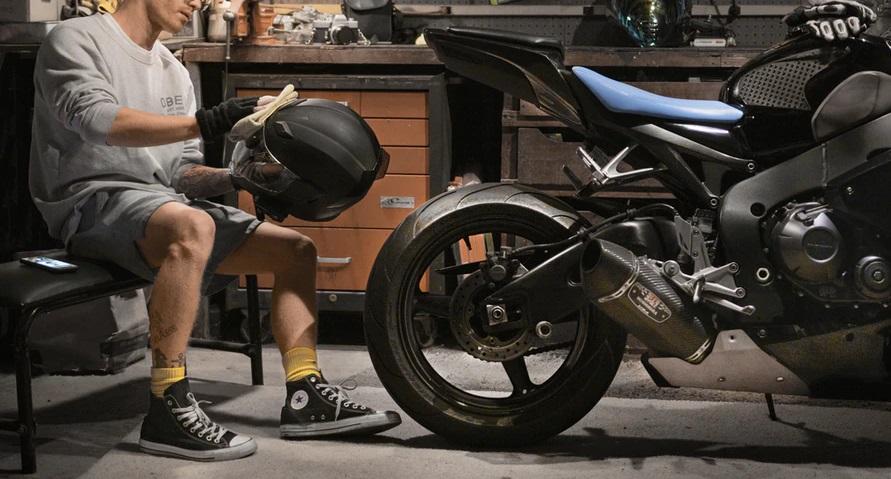 ガレージでバイクのヘルメットを磨き込む男性のいる風景
