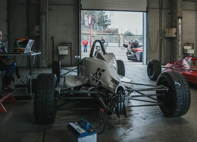 ガレージの中で整備中の白いフォーミュラカー