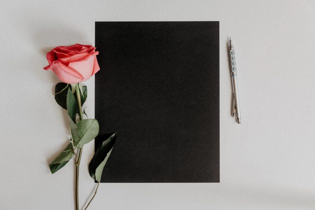 バラと黒いノートとペンが置かれたシックなデスク