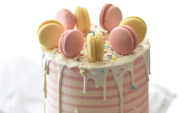 マカロンが沢山のったピンク色のポップなケーキ