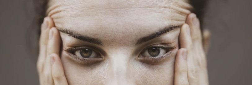 両手で目を広げる女性
