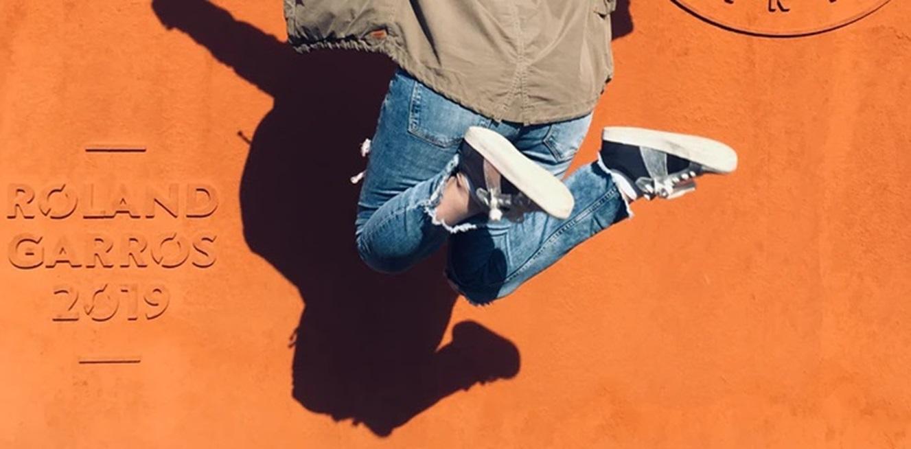 人_オレンジの壁の前でジャンプする女性