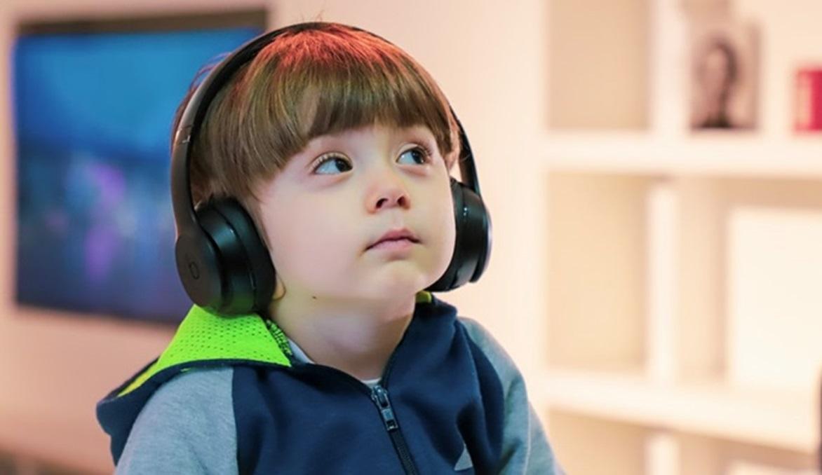 人_ヘッドフォンを耳にかけて、疑問を感じながら斜め上を見ている男の子