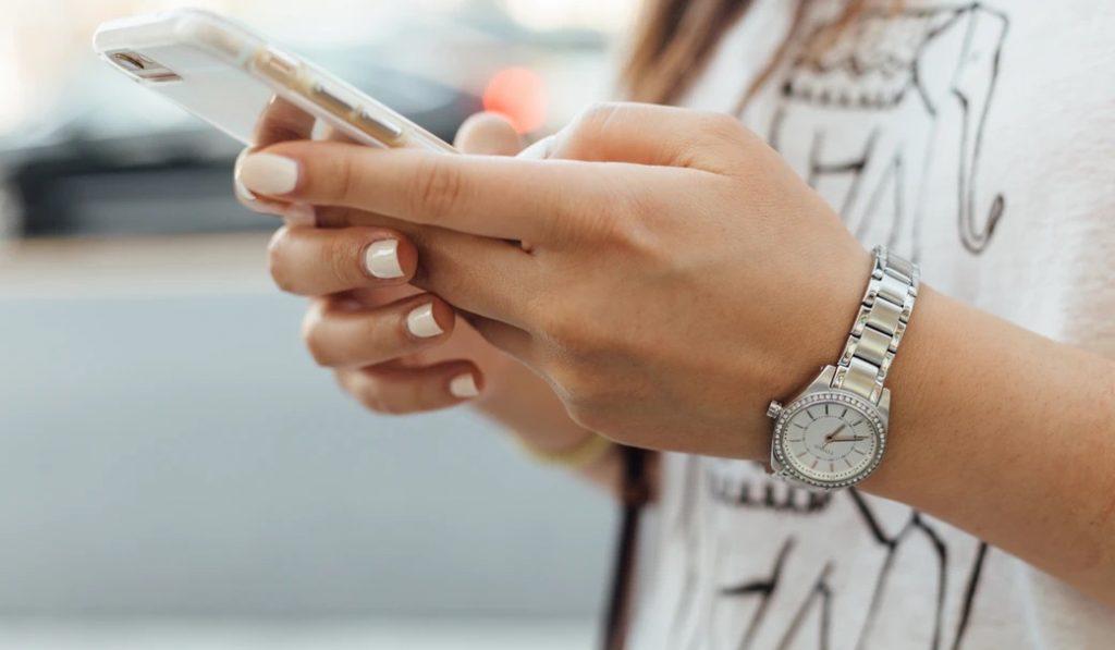 両手でスマートフォンを操作する女性の手元