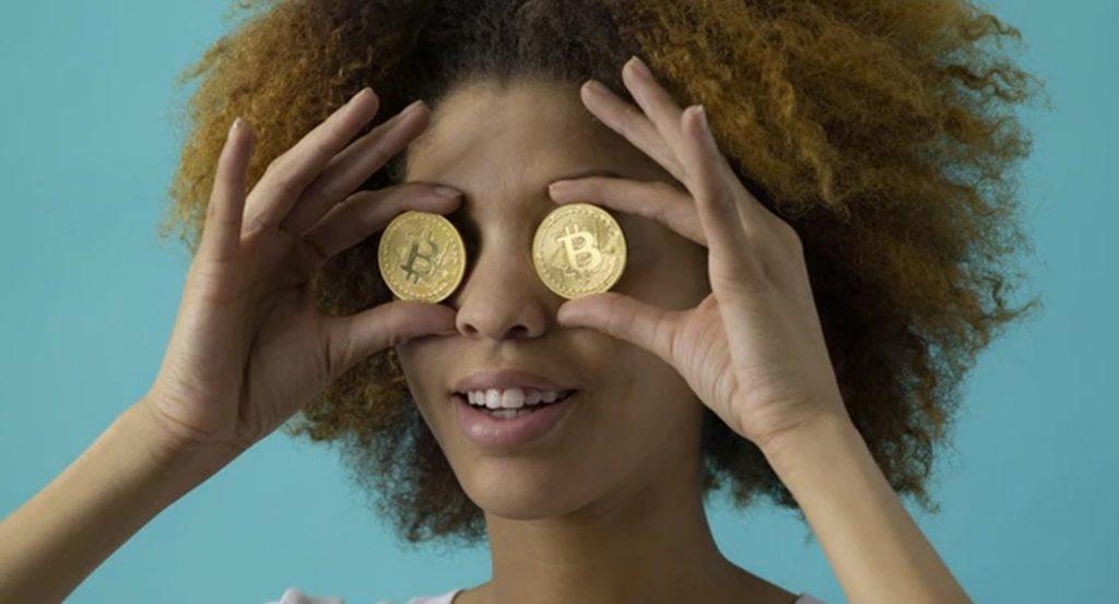 人_両目にビットコインを当てて遠くを見る表情の女性