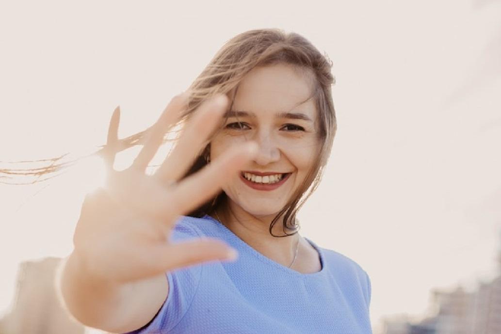 人_手のひらを見せて、視線を遮りながら優しく微笑む女性