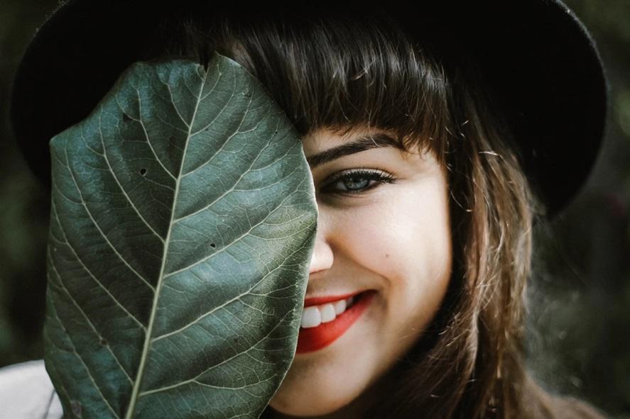 人_葉っぱの陰から微笑む女性
