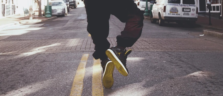 人_路上でジャンプする男性の足元
