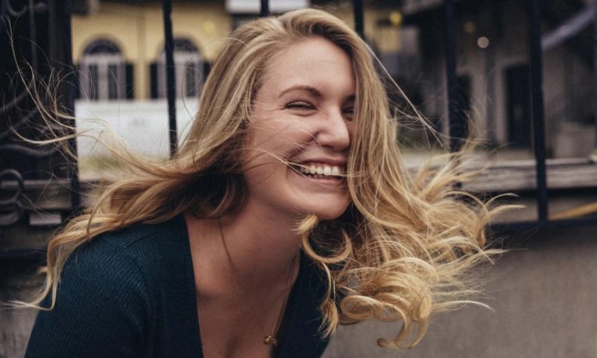 人_風に髪をなびかせて微笑む女性