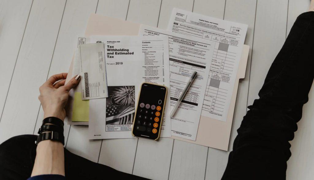 床に書類を広げ、税金計算とまとめを行う女性