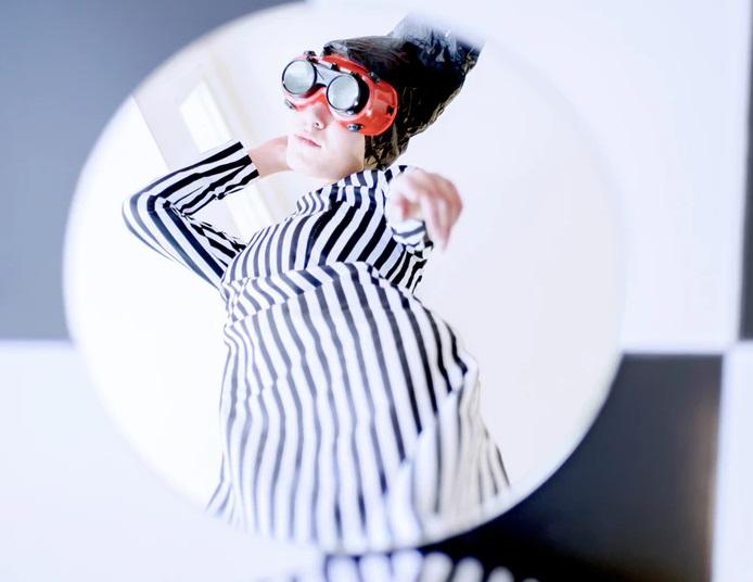 床に置いた鏡に映る自分を指さすストライプの服を着た女性
