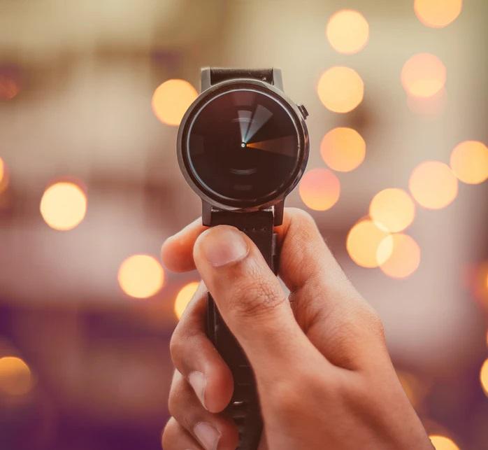 右手に持たれた黒い腕時計