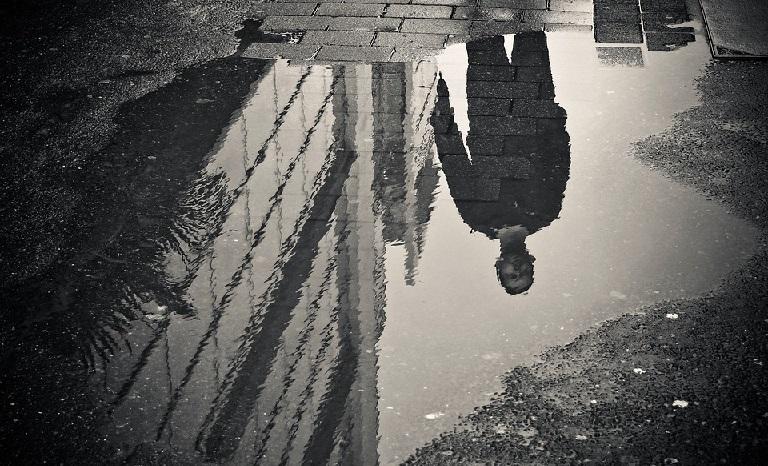 水たまりと水たまりに映った男性の画像