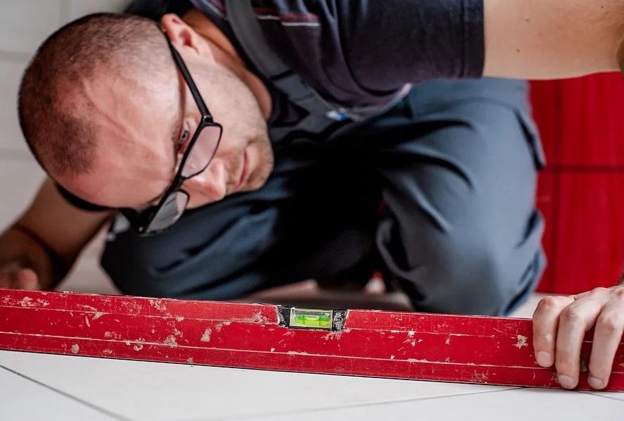 水平器をのぞきながら慎重に作業する業者の男性