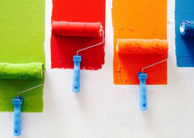 緑と赤とオレンジとブルーのペンキを4つのローラーで一気に塗り広げている風景