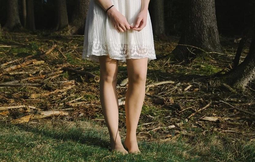 裸足で森の中にたたずむ女性の足元