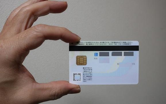 親指と小指で挟んで持たれたマイナンバーカード