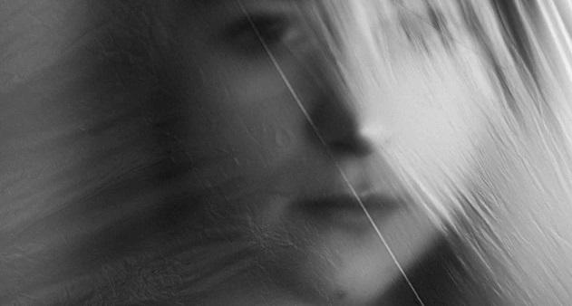 透明のビニール越しにこちらを見つめる、黒い瞳の女性