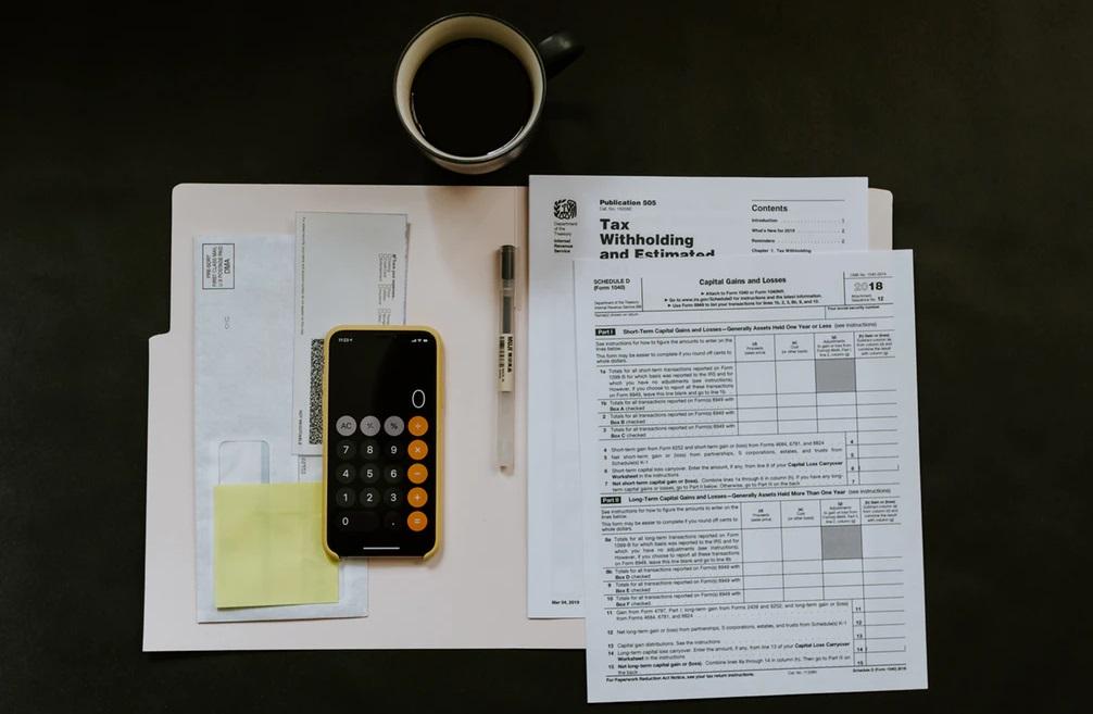 黒いテーブルに広げられた税金関係の書類をまとめたファルダと計算機とコーヒーなど