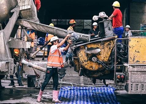 コンクリートミキサー車からコンクリートを流し込む作業員の居る風景
