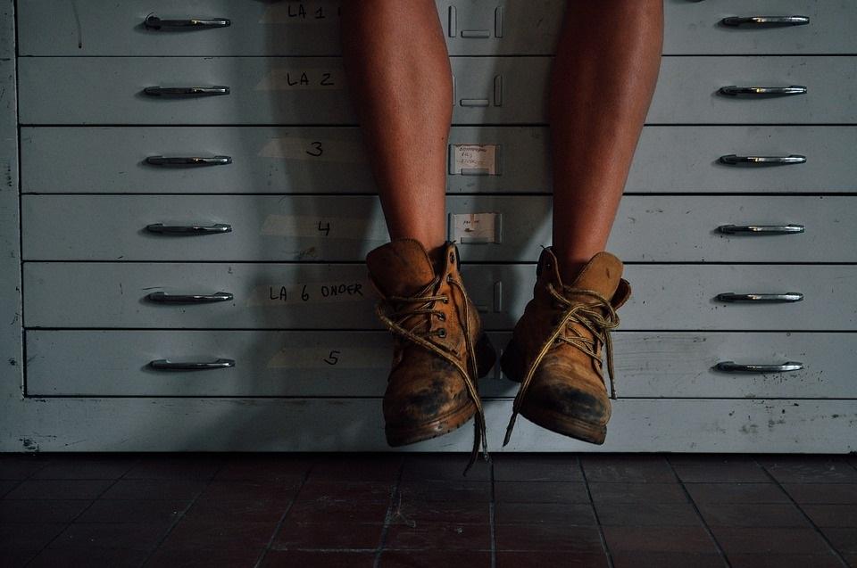 ブリキのキャビネットの前にぶらぶらと下げた汚れたブーツをはいた人の足元