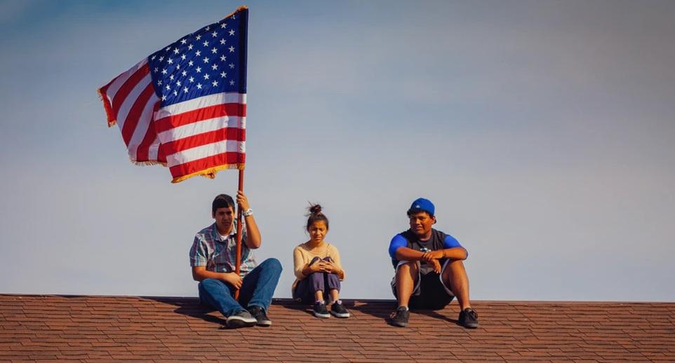 屋根上に上り、アメリカ国旗を掲げる3人の子供のいる風景