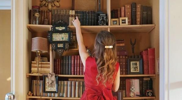本だなに手を伸ばす女の子