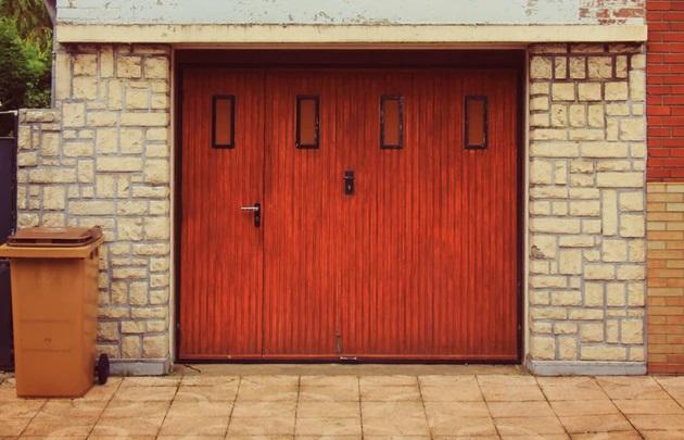 赤い扉の白いレンガ造りのガレージのある風景