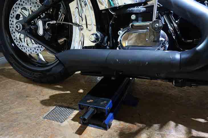 バイクの下にジャッキを挿入し、ジャッキアップしようとしている風景